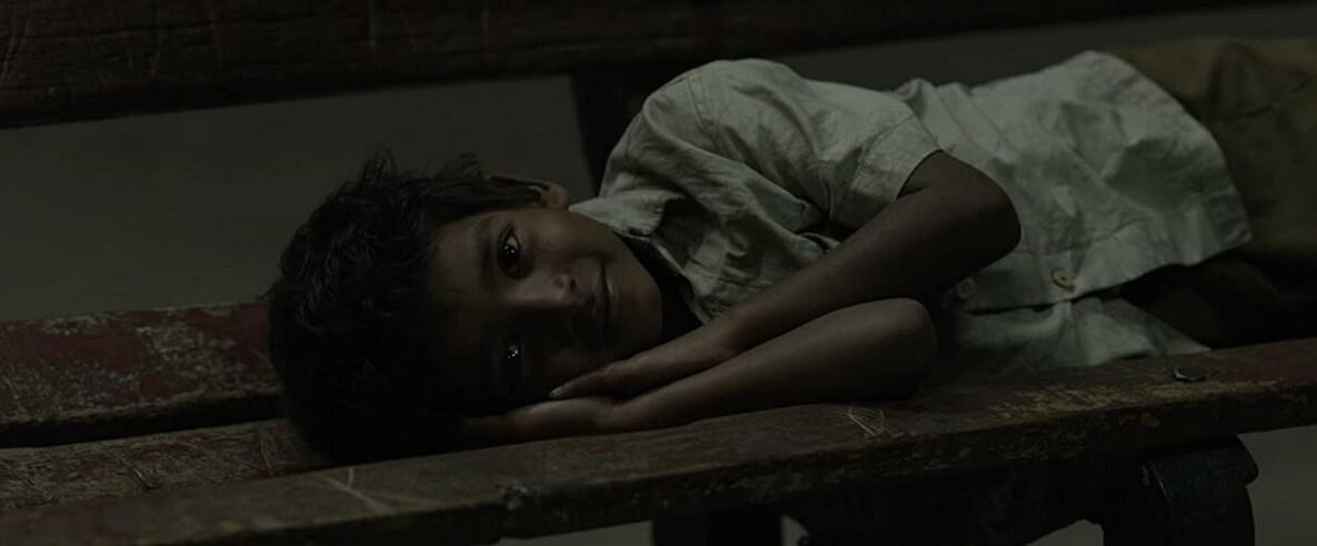 "boy lying on train station bench in ""Lion"""