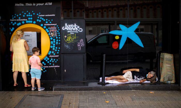A child looks at a man sleeping outside a CaixaBank brach office in Barcelona, Spain, on July 17, 2020. (Emilio Morenatti/ AP Photo)