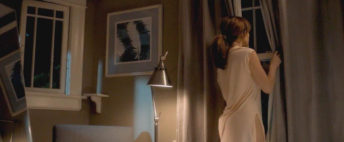 "woman in white dress peeps out window in ""The Boy Next Door"""