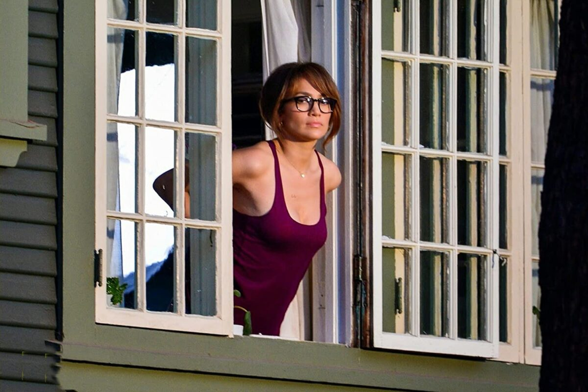 "woman in maroon tank-top and glasses at window in ""The Boy Next Door"""
