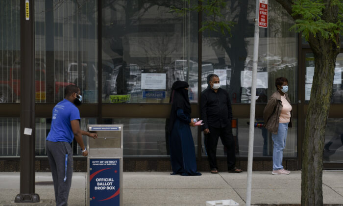 Residents keep their distance while waiting in line for same-day voter registration or amendments to their voting status as a man drops off his absentee ballot outside of the City of Detroit Department of Elections during the Michigan Primary Election in Detroit, Mich., Aug. 4, 2020. (Brittany Greeson/Getty Images)