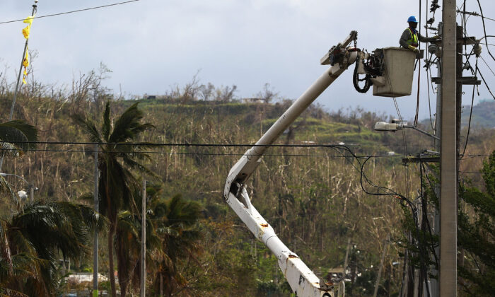 A worker repairs power lines about two weeks after Hurricane Maria in San Isidro, Puerto Rico. Puerto Rico, on Oct. 5, 2017. (Mario Tama/Getty Images)