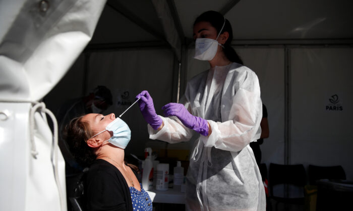 A health worker, wearing a protective suit and a mask, prepares to administer a nasal swab to a patient at a testing site for the COVID-19 in Paris, on Sept. 14, 2020. (Gonzalo Fuentes/Reuters)