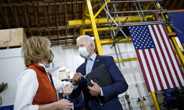 Democratic presidential nominee and former Vice President Joe Biden fist bumps Sen. Tina Smith (D-Minn.) after speaking and touring Jerry Alander Carpenter Training Center in Hermantown, Minn., on Sept. 18, 2020. (Drew Angerer/Getty Images)
