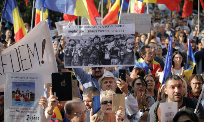 """A man holds a banner showing children in a concentration camp and a paraphrase from a statement by Romanian President Klaus Iohannis that reads """"Children get used to unpleasant things easily"""" during a protest in Bucharest, Romania, on Sept. 19, 2020. (Vadim Ghirda/AP Photo)"""