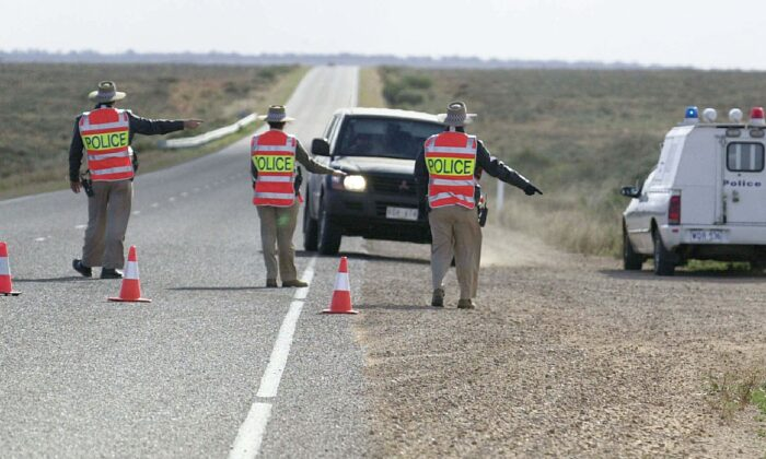 Police check cars at a road block north of Port Augusta, South Australia, on June 28, 2002. (ADELAIDE ADVERTISER/AFP via Getty Images)