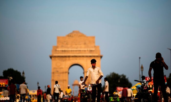 A vendor (C) wearing a mask looks for customers to ride his toy bike along the Rajpath street near India Gate in New Delhi on Sept. 16, 2020. (Jewel Samad/AFP via Getty Images)
