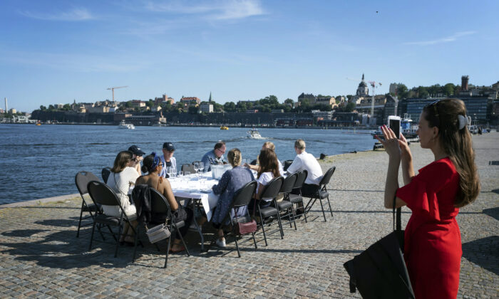 Employees socially distance due to the coronavirus as they have a drink after work, in Stockholm, on June 26, 2020. (Stina Stjernkvist/TT News Agency via AP Photo)