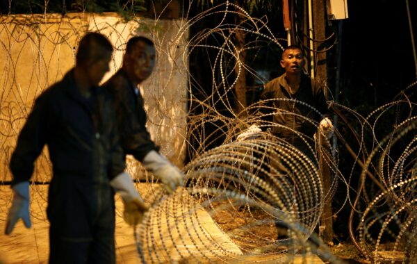 Security guards set up barbed wire