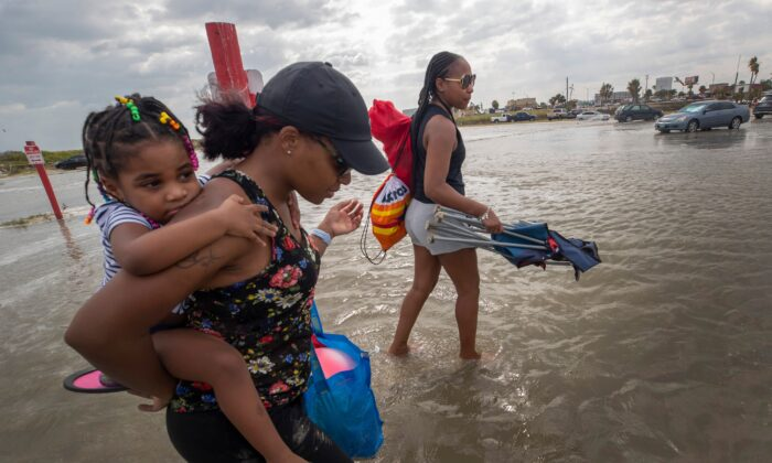 Stacey Young gives her daughter, Kylee Potts, a piggyback ride across the flooding Stewart Beach parking lot in Galveston, Texas, on Sept. 19, 2020. (Stuart Villanueva/The Galveston County Daily News via AP)