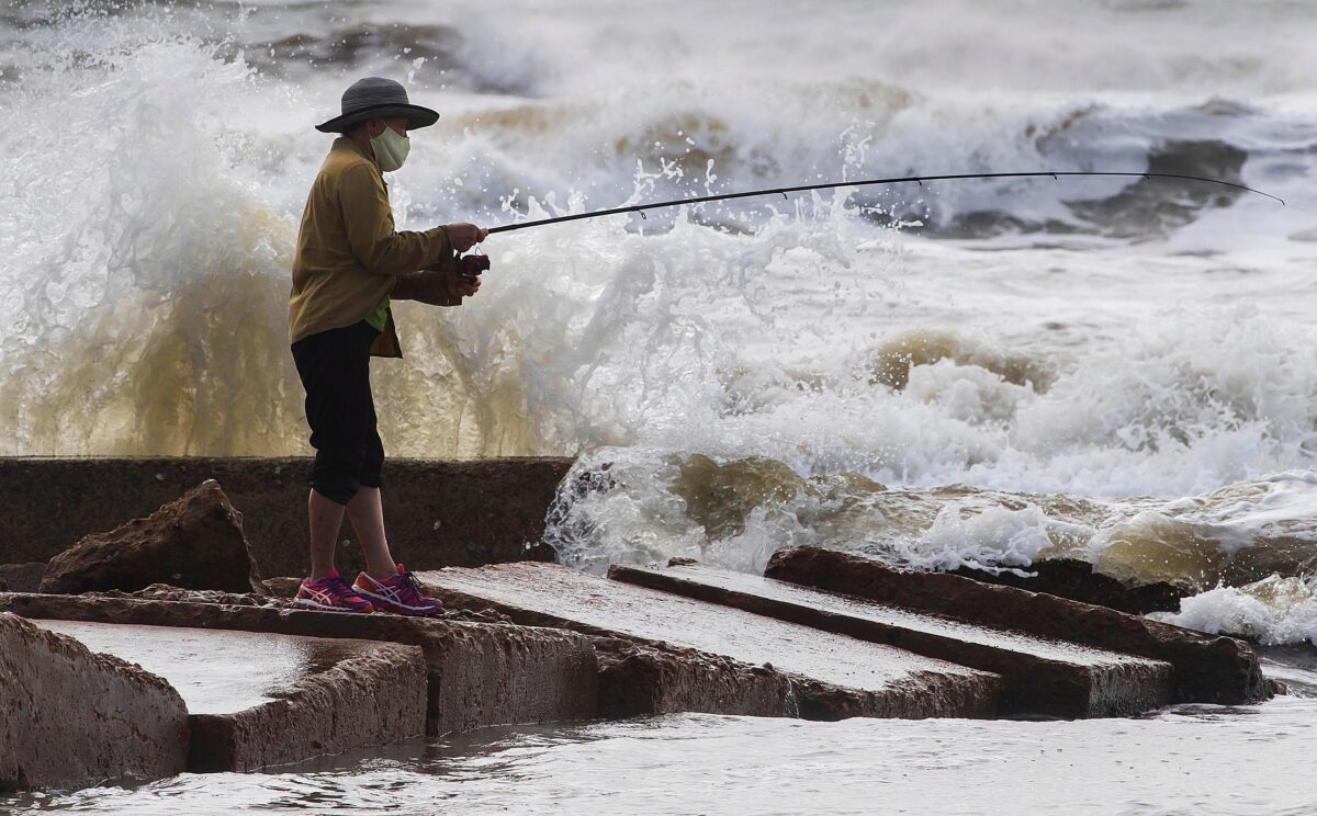 Waves crash as Houston resident Tinh Pham fishes