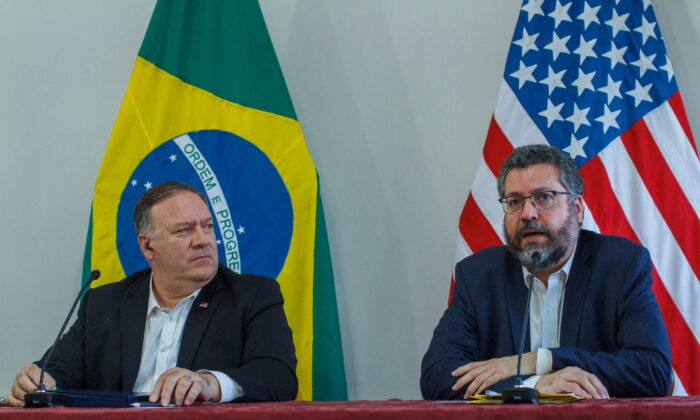U.S. Secretary of State Mike Pompeo looks at Brazilian Foreign Minister Ernesto Araujo speaking during a press conference at the Boa Vista Air Base in Roraima, Brazil, on Sept. 18, 2020. (Bruno Mancinelle/Pool via AP)