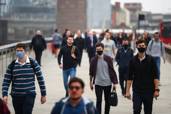 Commuters walk across London Bridge during the morning rush hour, amid an outbreak of the CCP virus in London