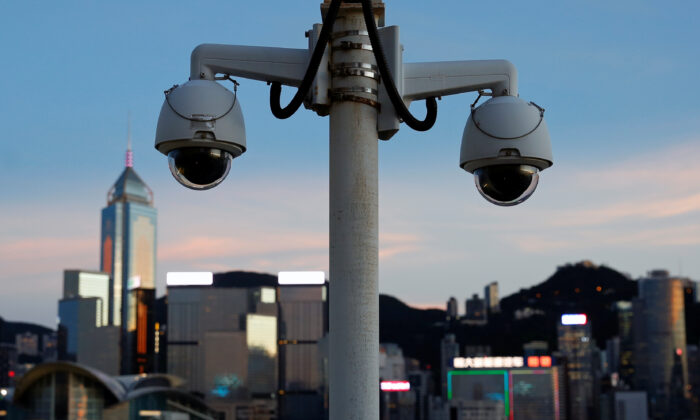A pair of surveillance cameras along the Tsim Sha Tsui waterfront as skyline buildings stand across Victoria Harbor in Hong Kong, on July 28, 2020. (Tyrone Siu/Reuters)
