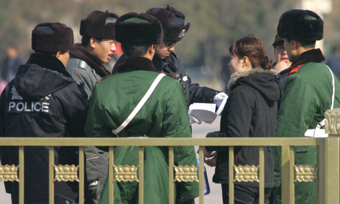 Police and paramilitary guards surround a woman while a policeman reads her petition amid tightened security on Tiananmen Square in Beijing on March 6, 2007. (FREDERIC J. BROWN/AFP via Getty Images)