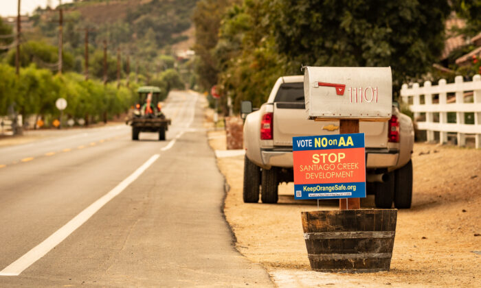 A tractor drives by a sign that urges voters to vote no on Measure AA, in front of a house in Orange, Calif., on Sept. 10, 2020. (John Fredricks/The Epoch Times)