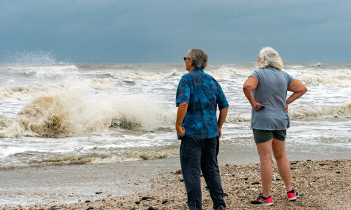 Steve and Linda Buser of Beaumont check out the rough surf on the beach near the intersection of Highway 124 and Highway 87 on the Bolivar Peninsula, Texas, on Sept. 20, 2020. (Fran Ruchalski/The Beaumont Enterprise via AP)