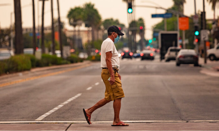 A man wearing a face mask crosses the street in Anaheim, Calif., on Sept. 9, 2020. (John Fredricks/The Epoch Times)