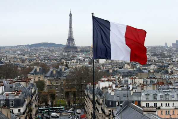 FILE PHOTO: A French flag waves above the skyline as the Eiffel Tower and roof tops are seen in Paris, France