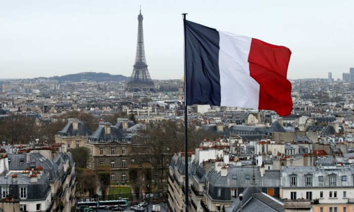 A city view shows the French flag above the skyline of the French capital as the Eiffel Tower and roof tops are seen in Paris, France, on March 30, 2016. (Benoit Tessier/Reuters)
