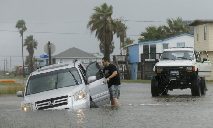 Jeff Williams gets back in his vehicle to try to get it out of the flooded road on Sept. 21, 2020, in Surfside, Texas. (Godofredo A. Vásquez/Houston Chronicle via AP)