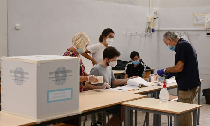 A man wearing a face mask and gloves (R) prepares to cast his vote at a polling station in downtown Rome on Sept. 20, 2020. (Vincenzo Pinto/AFP via Getty Images)