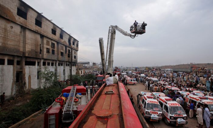 Ambulances and fire brigade vehicles outside a building after a fire at a garment factory in Karachi, Pakistan, on Sept. 12, 2012.  (Akhtar Soomro/File Photo/Reuters)