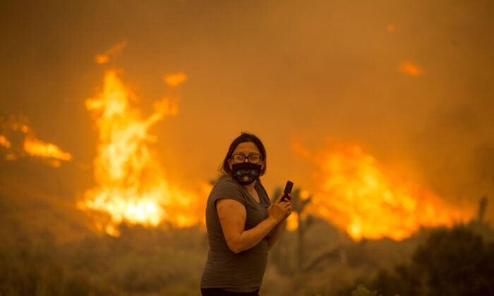 A woman watches as the Bobcat Fire burns in Juniper Hill, Calif., on Sept. 18, 2020. (Ringo H.W. Chiu/AP Photo)