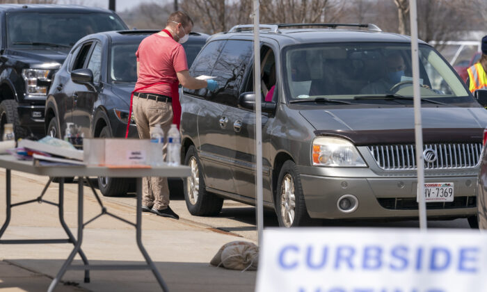 A poll worker talks to people during curbside voting in Sun Prarie, Wis., April 7, 2020. (Andy Manis/Getty Images)