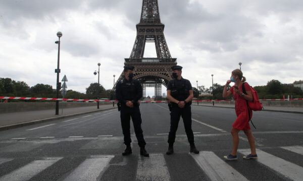 A woman walks past police officers securing the bridge leading to the Eiffel Tower