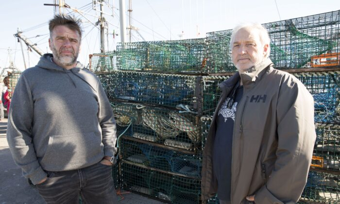 Colin Sproul (L), Bay of Fundy Inshore Fishermen's Association spokesman, and Bernie Berry, president of the Cold Water Lobster Coalition, pose in front of lobster traps that were seized in Saulnierville, N.S., on Sept. 20, 2020.  THE CANADIAN PRESS/Mark O'Neill