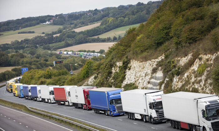 Heavy goods vehicles queue on a main road near Dover, southern England, after a police operation in the port city resulted in traffic congestion on nearby roads, on Sept. 16, 2020.  (Aaron Chown/PA via AP)