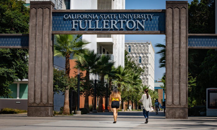 Students walk under the entry to the California State University–Fullerton campus in Fullerton, Calif., on Aug. 28, 2020. (John Fredricks/The Epoch Times)