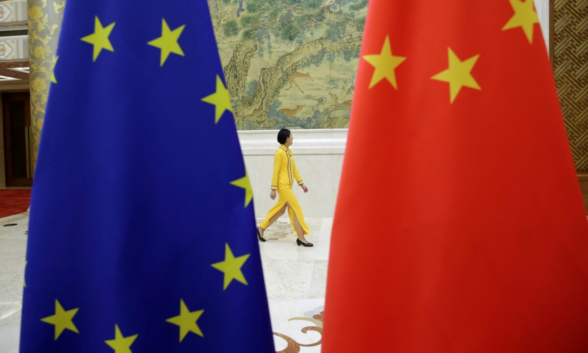 An attendant walks past flags of EU and China ahead of the EU-China High-level Economic Dialogue in Beijing