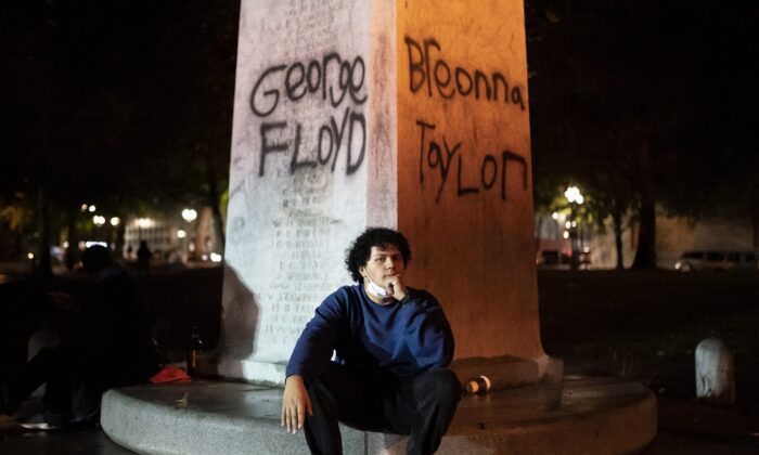 A protester catches his breath under the names of George Floyd and Breonna Taylor in Portland, Ore., on Sept. 23, 2020. (Nathan Howard/Getty Images)