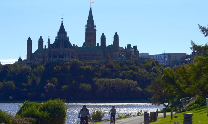 Cyclists ride along the Ottawa River as Parliament Hill looms in the background on Sept. 18, 2020. (The Canadian Press/Sean Kilpatrick)