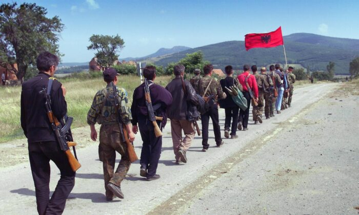Kosovo Liberation Army (KLA) fighters march down the mountains toward the Kosovar city of Lapusnik on Jun. 17, 1999. (Eric Feferberg/AFP via Getty Images)