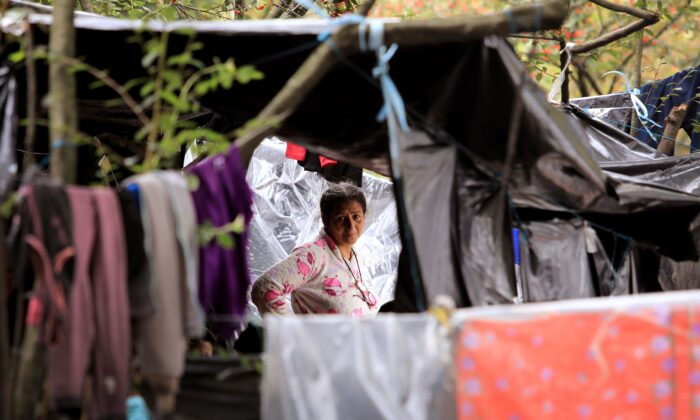 A woman stands at a makeshift camp where jobless and homeless Venezuelan migrants remain during the COVID-19 oronavirus pandemic, in Bogota, on June 17, 2020. (Daniel Munoz/AFP via Getty Images)