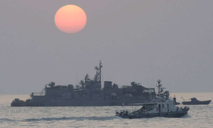A government ship sails past the South Korean Navy's floating base as the sun rises near Yeonpyeong island, South Korea on Dec. 22, 2010. (Ahn Young-joon/AP Photo)