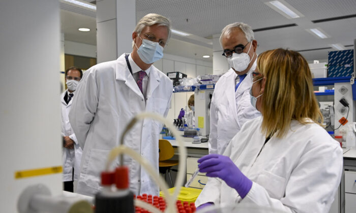King Philippe of Belgium (L) and Janssen Pharmaceutica chief scientific officer Paul Stoffels (C) talk to a scientist at work in the laboratory during a royal visit to the headquarters of Janssen Pharmaceutica in Beerse, Belgium, on June 17, 2020. (Dirk Waem/BELGA MAG/AFP via Getty Images)