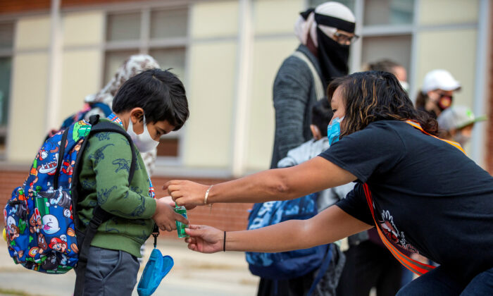 A teacher helps a student close his personal hand sanitizer as he arrives for the first time since the start of the coronavirus disease (COVID-19) pandemic at Hunter's Glen Junior Public School, part of the Toronto District School Board (TDSB) in Scarborough, Ontario, Canada September 15, 2020. (Reuters/Carlos Osorio/File Photo)