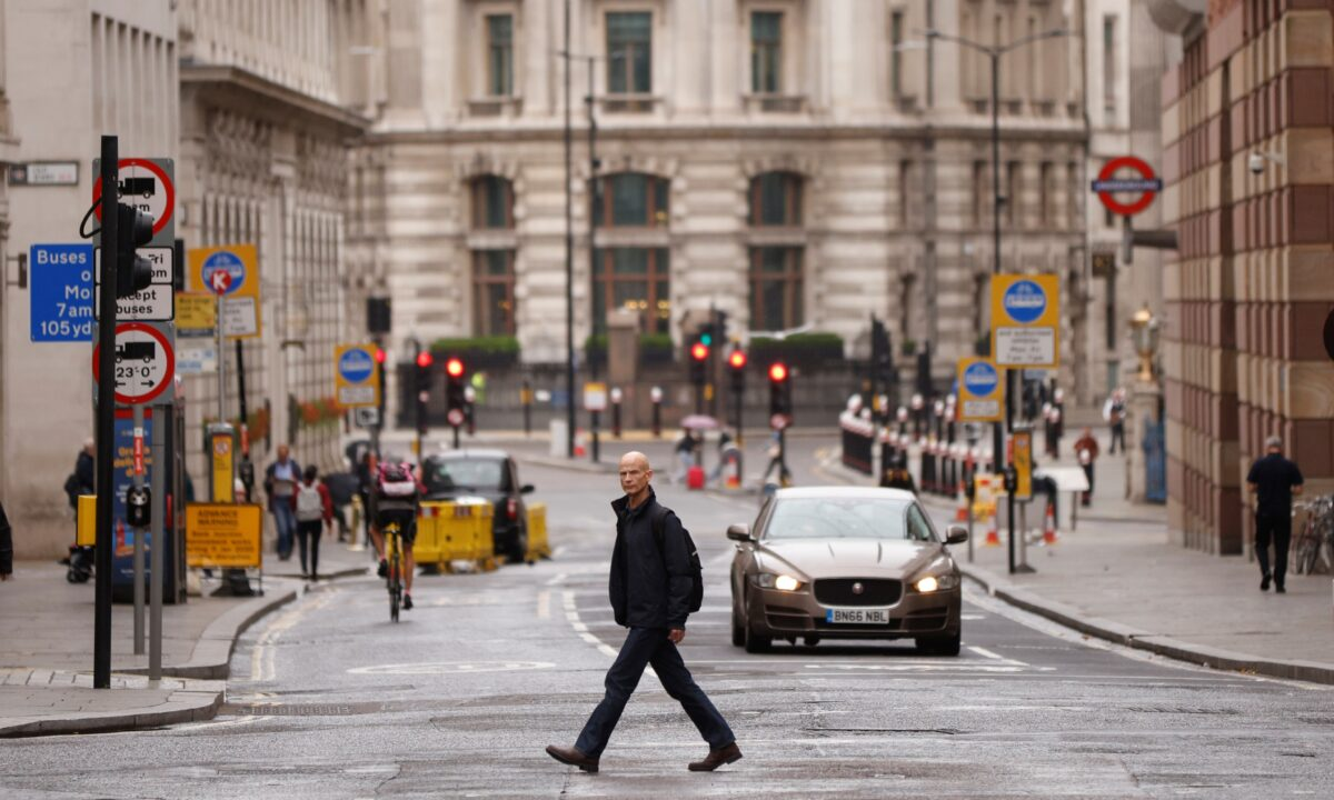 A man passes across the road in the City of Greater london financial district amid the particular outbreak of the coronavirus disease