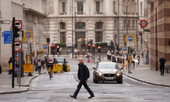 A man crosses the road in the City of London financial district amid the outbreak of the CCP virus, in London, on Sept. 23, 2020. (John Sibley/Reuters)