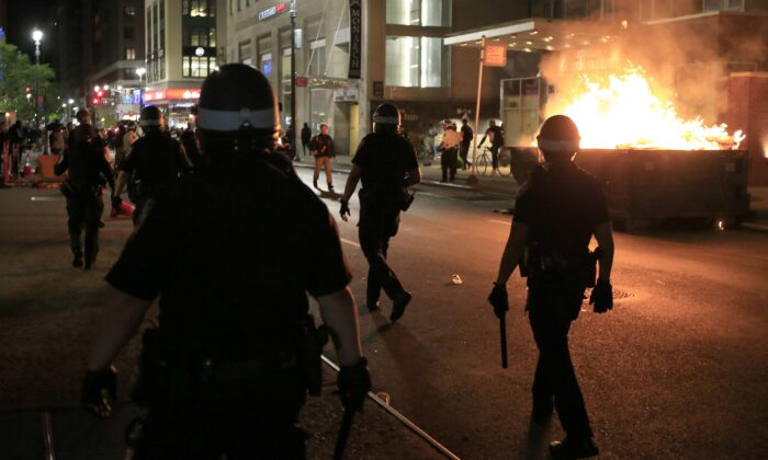 New York Police Department (NYPD) officers walk past a dumpster fire in front of the Hampton Inn in New York City on May 31, 2020. (Justin Heiman/Getty Images)