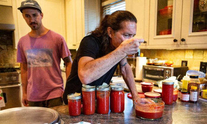 Gene Pietrini taste-tests some pizza sauce in his kitchen in Seal Beach, Calif., on Sept. 19, 2020. (John Fredricks/The Epoch Times)