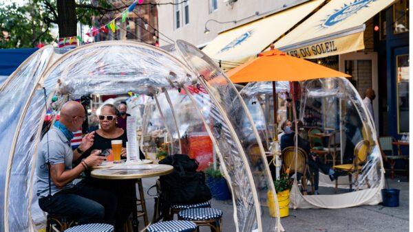 People sit under bubble tents