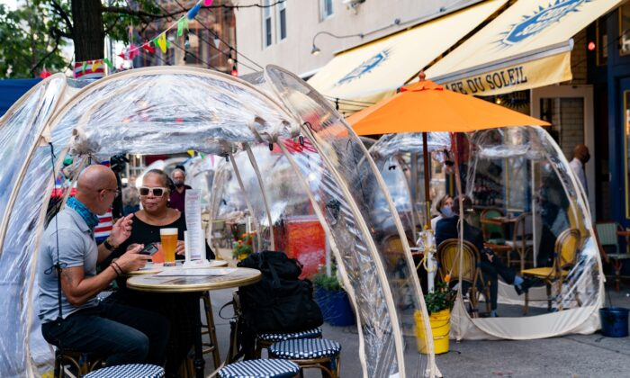 People sit outside Cafe Du Soliel under bubble tents in New York City, on Sept. 23, 2020. (Jeenah Moon/Reuters)