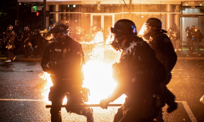 Portland police officers evade a Molotov cocktail amid rioting in Portland, Ore., on Sept. 23, 2020. (Mathieu Lewis-Rolland/Reuters)