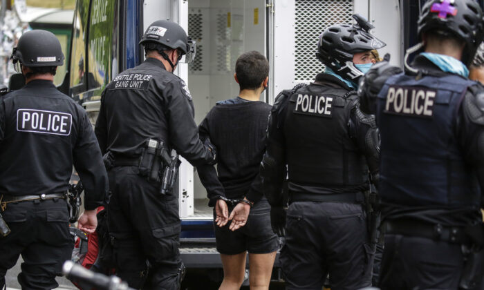 Seattle Police arrest a woman after demonstrators blocked the intersection of East Pine Street and 11th Avenue following the clearing of the Capitol Hill Occupied Protest (CHOP) by police in Seattle, Wash. on July 1, 2020. (Jason Redmond/AFP via Getty Images)