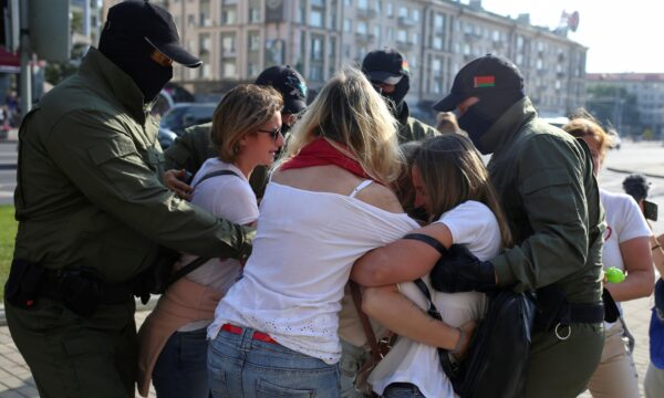 Belarusian law enforcement officers block women during an opposition rally